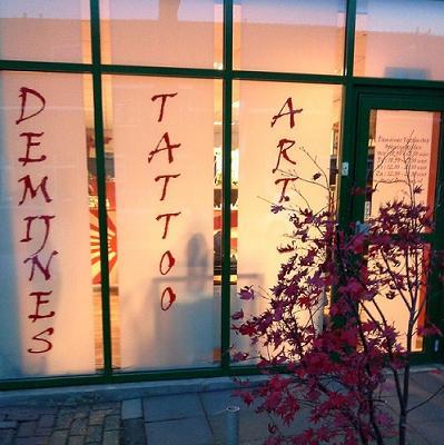 Foto van de tattooshop als het avond is. Je kijkt van buiten naar binnen.